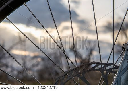 Blurred Sunset Sky Through The Spokes Of A Mountain Bike. Healthy Lifestyle Concept
