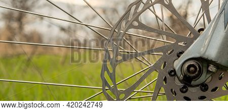 Part Of The Disc Brake And Spokes Of A Mountain Bike On A Blurred Background Of Green Grass Of A Lig