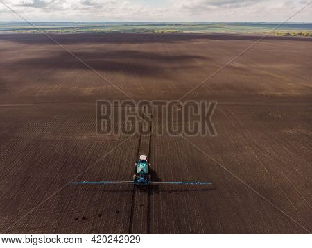Spring Agricultural Work In The Fields. The Tractor Sprays Crops With Herbicides, Insecticides And P