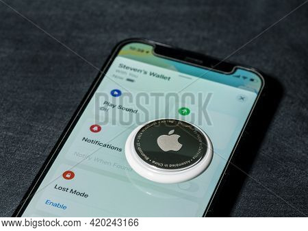 Morgantown, Wv - 12 May 2021: Apple Airtag Device Laying On Screen Of Iphone Mini Smartphone
