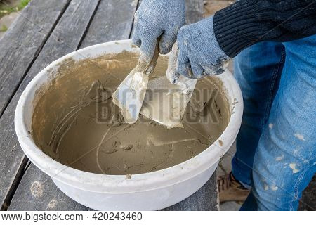 Masonry Works. Working Hands In Blue Gloves With A Trowel.