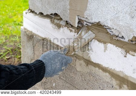 Masonry Works. Working Hand In Blue Glove With A Trowel.