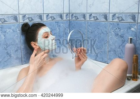 Portrait Og Young Woman Is Applying Alginate Mask In Bathr With Foam Looking At Small Mirror At Home