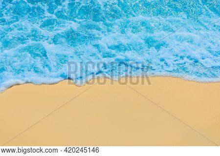 Blue Seaside Water On Light Yellow Beach Sand Coastline Seashore Background.