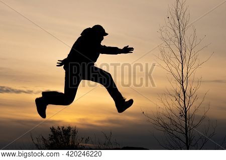 Silhouette Of A Man Running In Flight And Silhouette Of A Tree Without Leaves, Autumn Runaways