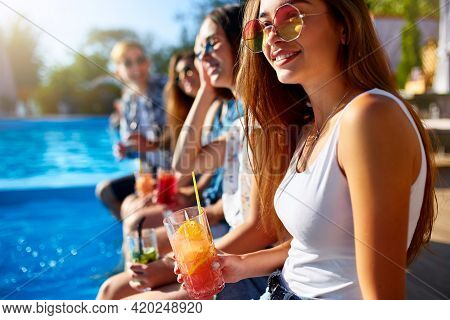 Pretty Woman Relax With Fresh Colorful Cocktail Glass Sitting By Swimming Pool On Sunny Summer Day W