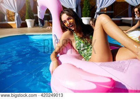 Young Hot Girl Having Fun And Laughing On An Inflatable Pink Flamingo Pool Float Mattress In Bikini.