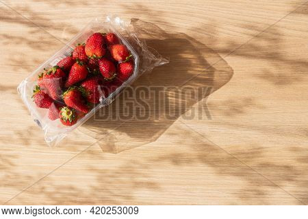 Strawberries In A Plastic Packaging On Wooden Background On A Sunny Day. Red Berries Seasonal Fruit