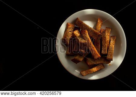 Rye Croutons On A White Plate Isolated On A Black Background. Bread With Croutons On A White Plate.