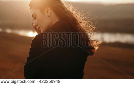 Side View Of Tranquil Female Standing Near Pond At Sunset In Back Lit On Windy Day