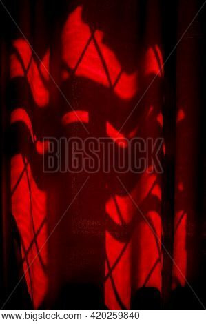 Red Curtain On The Window. Lines Of Light On Red Developing Tissue. Shadow On The Curtain From The W