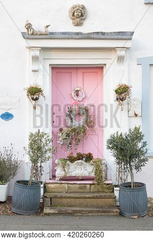 Buckinghamshire, Uk - December 25, 2020. Ornate Pink Front Door Of Period House Decorated With A Chr