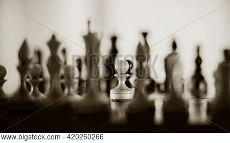 White Pawn And Silhouettes Of Chess Pieces. Wooden Chess Pieces On The Chessboard. Intellectual Game