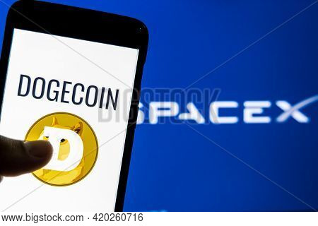 Kathmandu, Nepal - May 11 2021: Dogecoin Logo On A Smartphone Against Spacex Logo In The Background.