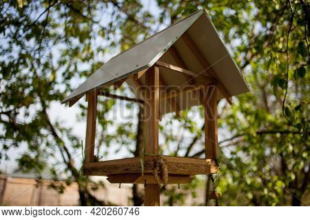 Wooden Birdhouse On A Background Of Foliage. Brown Wooden Birdhouse With Foliage Blurred In Backgrou