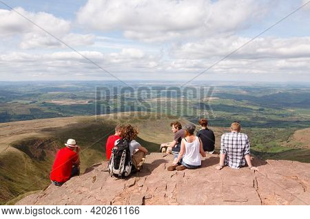 Brecon Beacons, Uk - April 25, 2011. Mixed Group Of Young Caucasian People, Hikers Sitting On The Pe