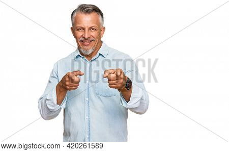 Middle age grey-haired man wearing casual clothes pointing fingers to camera with happy and funny face. good energy and vibes.