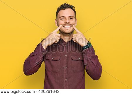 Young hispanic man wearing casual clothes smiling with open mouth, fingers pointing and forcing cheerful smile