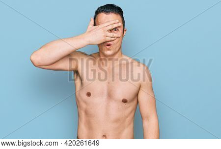 Handsome young man wearing swimwear shirtless peeking in shock covering face and eyes with hand, looking through fingers with embarrassed expression.