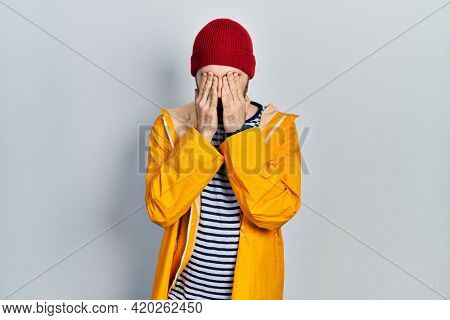 Caucasian man with beard wearing yellow raincoat rubbing eyes for fatigue and headache, sleepy and tired expression. vision problem