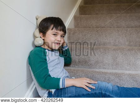 Happy Asian Boy Sitting On Staircase Playing With Teddy Bear In The Morning, Funny Kid Playing With