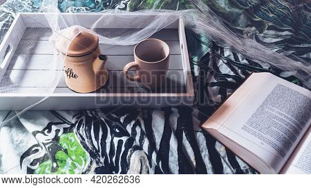 Image Of A Wooden Tray With A Coffee Pot And Mug Sitting On A Bed Inside A Mosquito Net. On The Bed