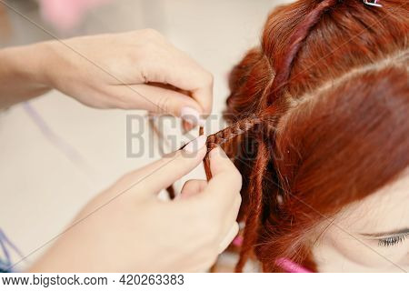 Hairdresser Weaves Woman Ginger Dreadlocks. Close Up Of Braiding Process African Plaits With Colored