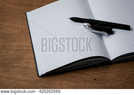 Open Notepad In A Cage On A Wooden Table With A Pen. Open The Notebook On The Office Desk. Outdoor N