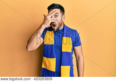 Young hispanic man football hooligan cheering game peeking in shock covering face and eyes with hand, looking through fingers afraid
