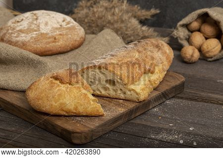 Fresh Crispy Baguette On A Wooden Board. Sliced Traditional French Bread. Close-up