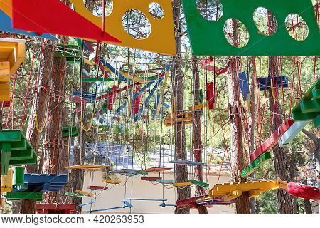 Rope Park. Bright Colored Boards Of The Climbing Attraction In The Air On The Trees.