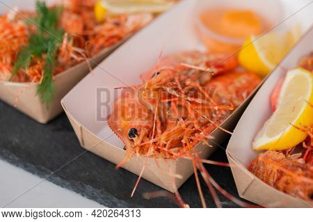 Cooked Fresh Red Langoustine Shrimps, Prawns With Lemon And Sauce In Paper Take Out Box At Summer Lo