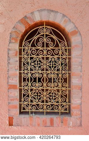 Photo Of A Window With Wrought Iron Covering In Pink Wall In Marrakesh Morocco
