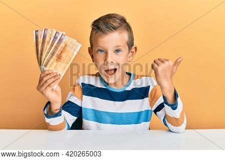 Adorable caucasian kid holding 500 norwegian krone banknotes sitting on the table pointing thumb up to the side smiling happy with open mouth