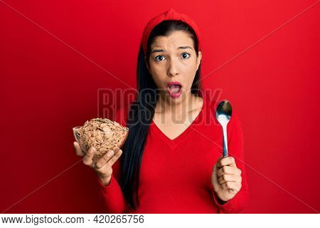Young latin woman holding cornflakes and spoon afraid and shocked with surprise and amazed expression, fear and excited face.