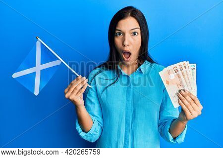 Young latin woman holding scotland flag and pounds banknotes afraid and shocked with surprise and amazed expression, fear and excited face.