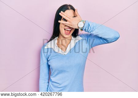 Beautiful woman with blue eyes standing over pink background peeking in shock covering face and eyes with hand, looking through fingers with embarrassed expression.