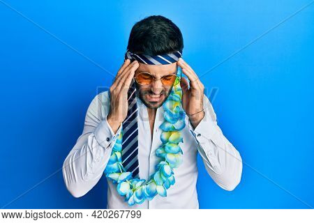 Young hispanic businessman wearing party funny style with tie on head with hand on head for pain in head because stress. suffering migraine.