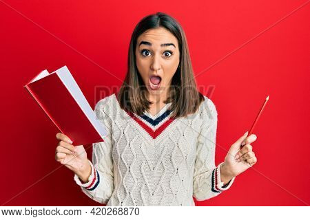Young brunette girl holding book and pencil afraid and shocked with surprise and amazed expression, fear and excited face.