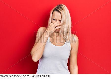 Beautiful caucasian blonde woman wearing casual white t shirt smelling something stinky and disgusting, intolerable smell, holding breath with fingers on nose. bad smell