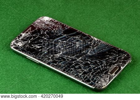 Shattered Cellphone On A Green Felt Table Top