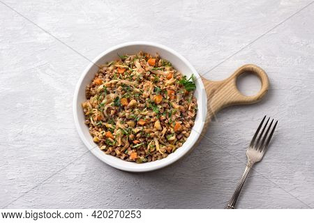 Delicious Vegetarian Buckwheat With Cabbage, Carrots, Onions, Nuts And Herbs On A Light Gray Texture