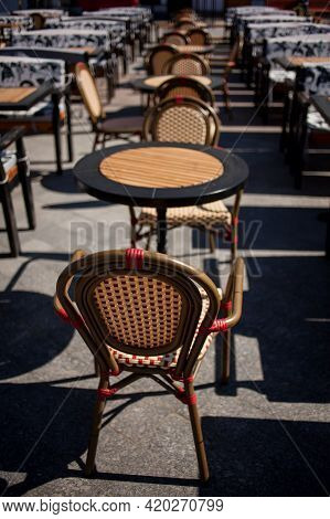 Wicker Chairs And Tables, Cafes. Outdoor Traditional Cafe With Old Wood Tables And Wicker Chairs. Wi