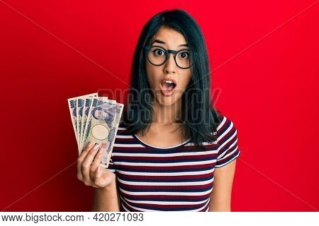 Beautiful asian young woman holding 5000 japanese yen banknotes scared and amazed with open mouth for surprise, disbelief face