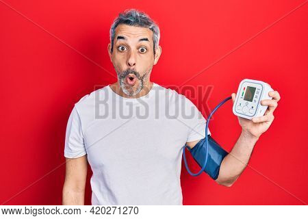 Handsome middle age man with grey hair using blood pressure monitor scared and amazed with open mouth for surprise, disbelief face