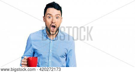 Hispanic man with beard drinking a cup coffee scared and amazed with open mouth for surprise, disbelief face