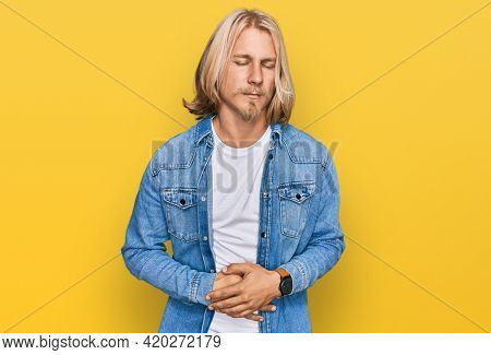 Caucasian man with blond long hair wearing casual denim jacket with hand on stomach because indigestion, painful illness feeling unwell. ache concept.