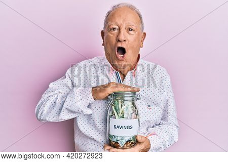 Senior caucasian man holding jar with savings afraid and shocked with surprise and amazed expression, fear and excited face.