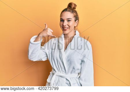 Young blonde woman wearing bathrobe smiling doing phone gesture with hand and fingers like talking on the telephone. communicating concepts.