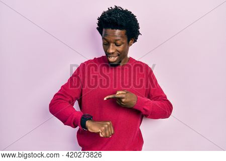 Young african american man wearing casual clothes in hurry pointing to watch time, impatience, upset and angry for deadline delay